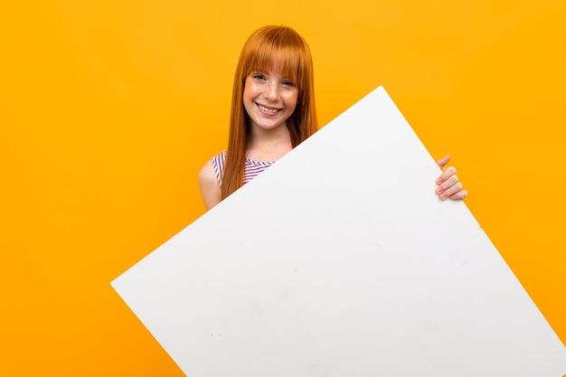 Schöne kaukasische frau mit roten haaren arbeitet mit großer weißer platte lokalisiert auf gelbem hintergrund.