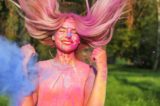 Schöne kaukasische frau mit vom wind aufgeblähten haaren, die mit trockener farbe spielt holi