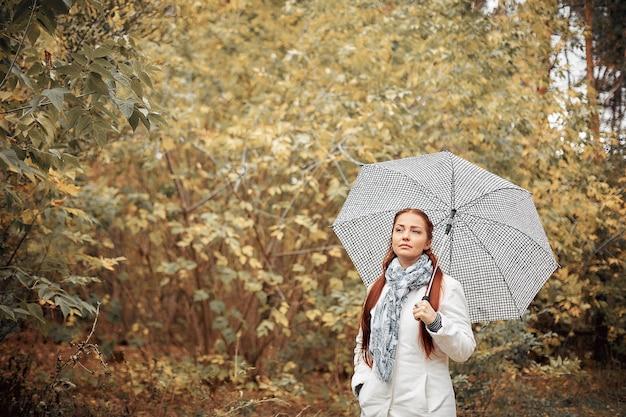 Schöne kaukasische frau mittleren alters mit roten haaren mit einem regenschirm im park an einem wolkigen herbsttag.