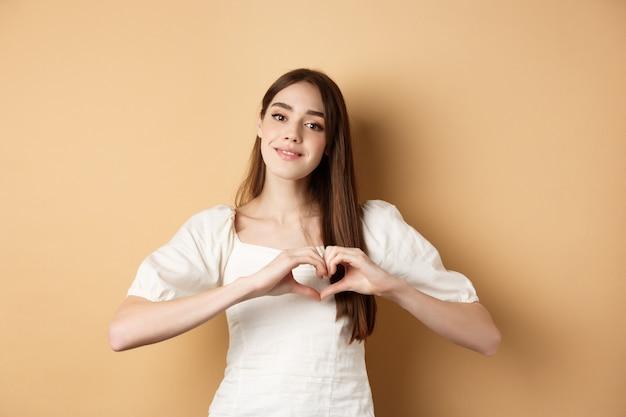 Schöne kaukasische frau sagt, ich liebe dich, zeigt eine herzgeste und lächelt auf den beigen hintergrund der kamera ...