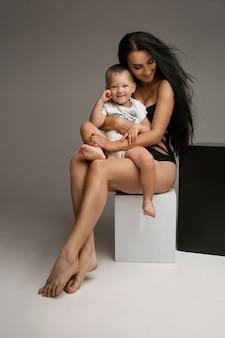 Schöne kaukasische frau sitzt auf einem schwarzen und weißen würfel und umarmt ihr kind, bild auf weiß
