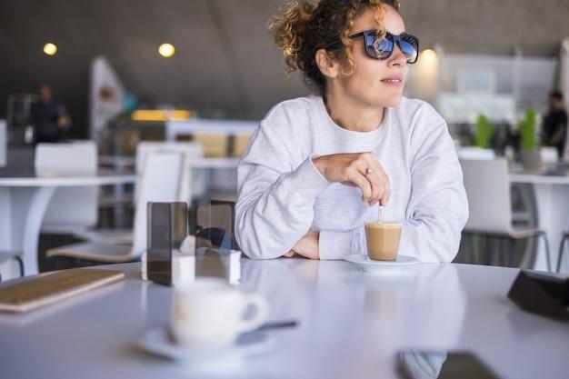 Schöne kaukasische frauen mittleren alters mit sonnenbrille nehmen und trinken einen kaffee in einer bar. außenlicht aus dem fenster für einen erholsamen moment während des tages. ruhig und entspann dich