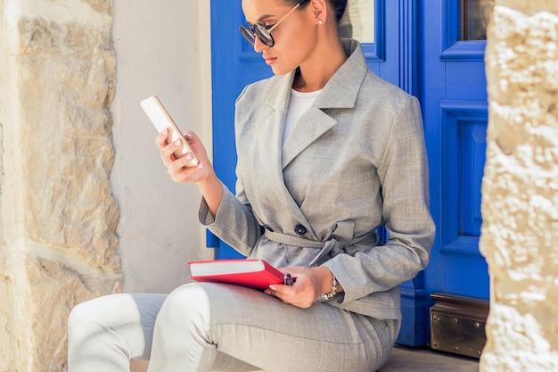 Schöne kaukasische geschäftsfrau, die smartphone verwendet, das nahe tür draußen sitzt.