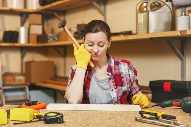 Schöne kaukasische junge braunhaarige frau in kariertem hemd, grauem t-shirt, gelben handschuhen, die in der tischlerei am holztisch mit stück eisen und holz arbeiten, verschiedene werkzeuge. nagel hämmern.