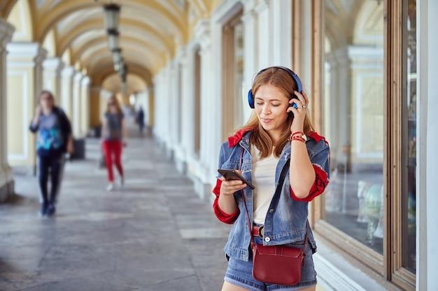 Schöne kaukasische junge frau ungefähr 25 jahre alt in modischem stoff hört musik mit hilfe von kopfhörern und smartphone und lächelt, während sie in der handelsgalerie geht.