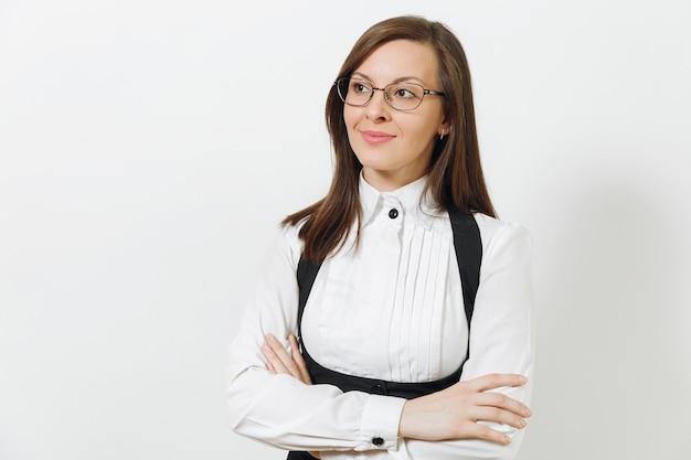 Schöne kaukasische junge lächelnde braunhaarige geschäftsfrau im schwarzen anzug, im weißen hemd und in den gläsern, die händchen halten, kreuzten lokalisiert auf weißem hintergrund. manager oder arbeiter. kopieren sie platz für werbung.