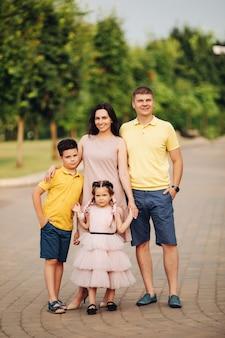 Schöne kaukasische mama, papa, ihr sohn und ihre tochter, die im sommer zusammen im park spazieren gehen