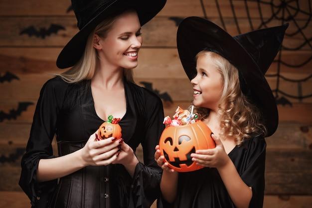 Schöne kaukasische mutter und ihre tochter in hexenkostüme halloween feiern mit teilen halloween süßigkeiten