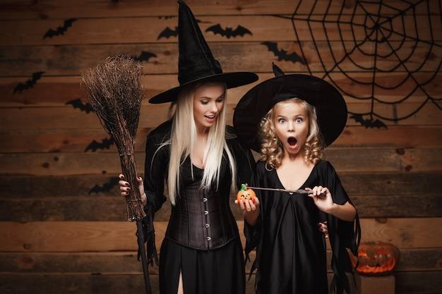 Schöne kaukasische mutter und ihre tochter in hexenkostümen genießen magie mit zauberstab zu halloween kürbisglas verwenden