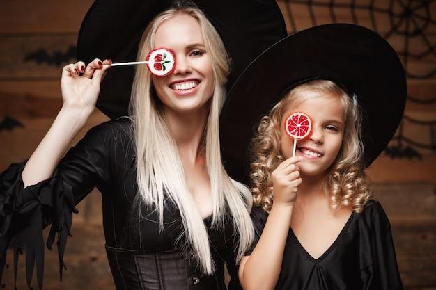 Schöne kaukasische mutter und ihre tochter in hexenkostümen halloween mit halloween süßigkeiten zu feiern
