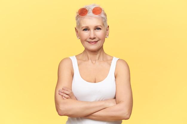 Schöne kaukasische pensionierte frau, die runde rosa sonnenbrille und weißes trägershirt trägt, arme auf ihrer brust kreuzend, selbstbewussten gesichtsausdruck habend.