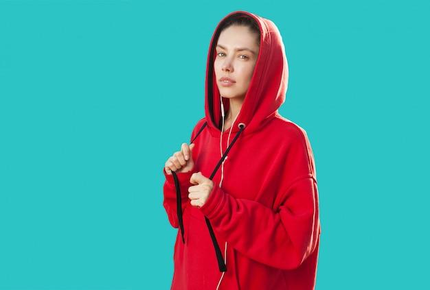 Schöne kaukasische sportliche frau zum modischen roten hoodie