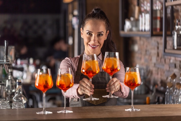 Schöne kellnerin, die gläser frisch zubereiteten aperol-spritz-cocktails anbietet. Premium Fotos