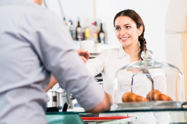 Schöne kellnerin, die männlichen kunden mit einer tasse kaffee dient