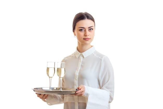 Schöne kellnerin mit champagner auf einem trey in die kamera schaut isoliert auf weißem hintergrund