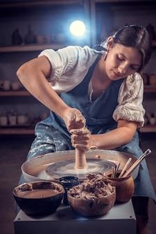 Schöne keramikerin, die eine tonvase auf einer töpferscheibe formt. handwerk.