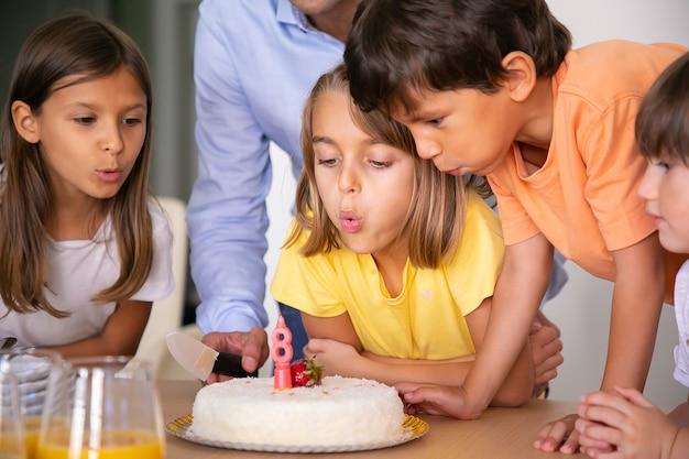 Schöne kinder, die kerze ausblasen und sich wünschen. blondes kaukasisches mädchen, das ihren geburtstag mit freunden und kuchen feiert. glückliche kinder, die spaß zusammen haben. kindheits-, feier- und feiertagskonzept