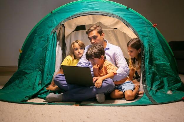 Schöne kinder, die mit vater im zelt zu hause entspannen und film auf laptop-computer schauen. nette kinder und vater mittleren alters sitzen und haben spaß zusammen. kindheits-, familienzeit- und wochenendkonzept