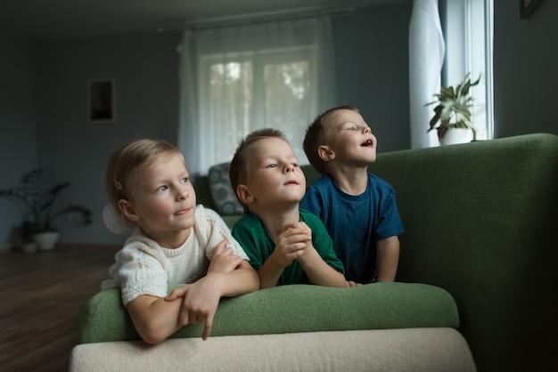 Schöne kinder, die zu hause auf dem sofa liegen, schauen neugierig aus dem fenster. .