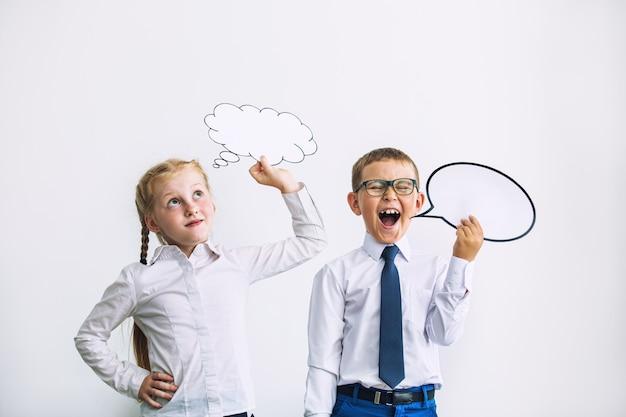 Schöne kinder jungen und mädchen mit gedankenzeichen aus comics zusammen in schuluniform glücklich auf weißem hintergrund