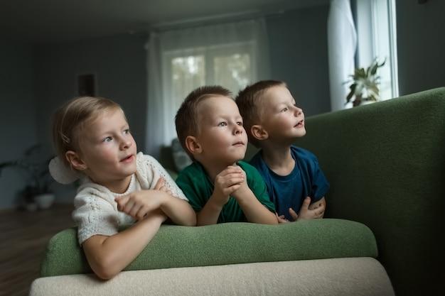 Schöne kinder liegen zu hause auf dem sofa und schauen neugierig zur seite. .