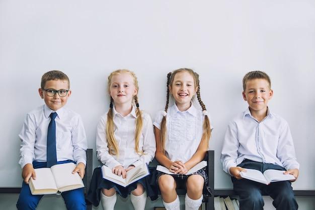 Schöne kinder mit büchern, die zusammen im klassenzimmer in der schule in uniform studiert wurden, werden glücklich erzogen