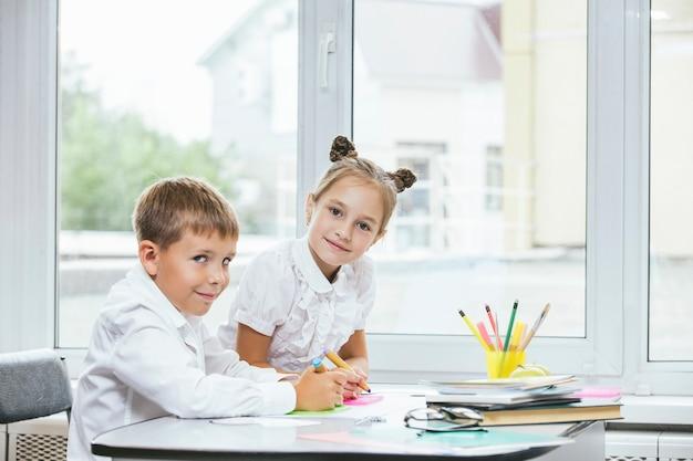 Schöne kinder sind schüler, die zusammen in einem klassenzimmer der schule eine glückliche ausbildung erhalten