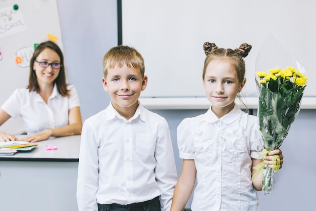 Schöne kinderschulkinder mit blumen für die lehrer an der schule im urlaub