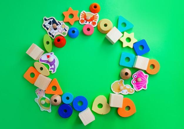 Schöne kinderspielzeuge sind auf einer grünen hintergrundoberansicht ausgelegt. platz für text