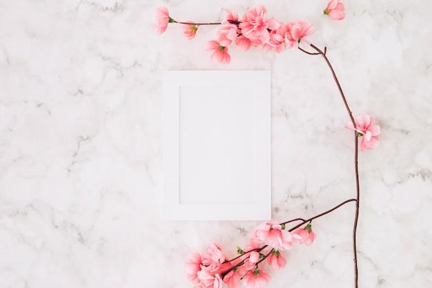 Schöne kirschblüte kirschblüte im frühjahr nahe dem weißen leeren bilderrahmen auf strukturiertem hintergrund