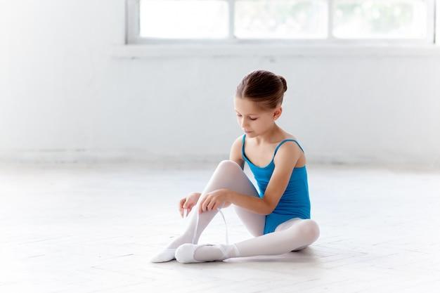Schöne kleine ballerina im blauen kleid, das sich zu fuß pointe schuhe setzt