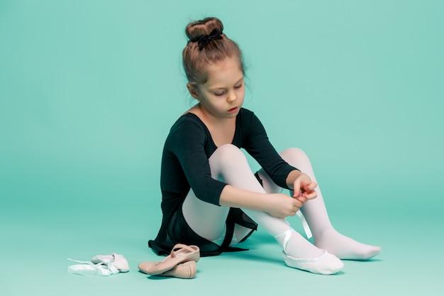 Schöne kleine ballerina im schwarzen kleid zum tanzen auf dem boden sitzend und auf fuß spitzenschuhe auf blauem studio anziehen