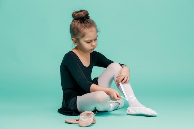 Schöne kleine ballerina im schwarzen kleid zum tanzen, die fußspitzenschuhe anzieht