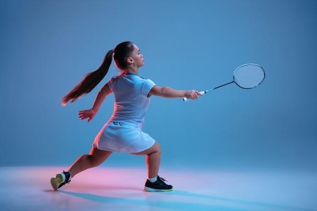 Schöne kleine frau, die im badminton übt