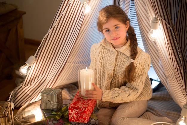 Schöne kleine frau, die mit einer brennenden kerze in seinen händen weihnachten sitzt