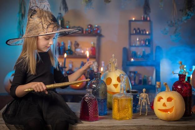 Schöne kleine hexe mit halloween-dekorationen