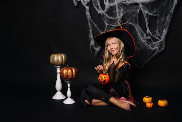 Schöne kleine hexe mit jack-o-lantern
