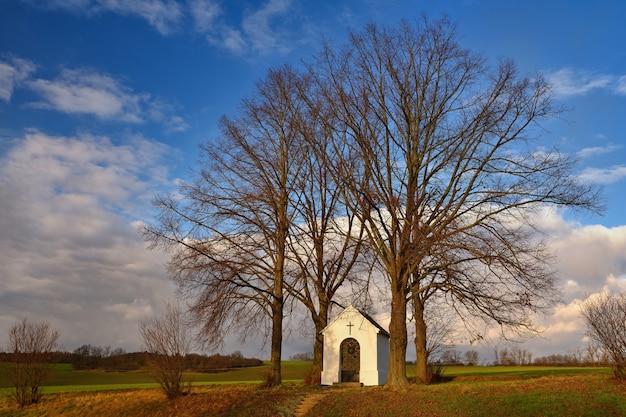 Schöne kleine kapelle mit landschaft und bäumen bei sonnenuntergang. nebovidy - tschechische republik.