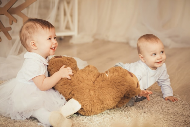 Schöne kleine kinder mit einem weichen braunen teddybär im innenraum mit weihnachtsdekorationen
