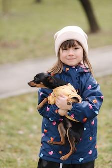 Schöne kleine mädchen gehen mit niedlichen hund im freien sechs jahre altes mädchen umarmen ihr haustier