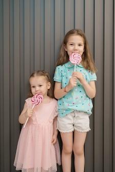 Schöne kleine mädchen mit lollypop auf grauem hintergrund
