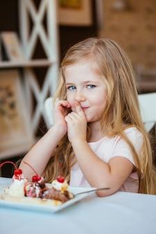 Schöne kleine mädchenblondine, die im café lächelt, isst ein desserteis mit früchten