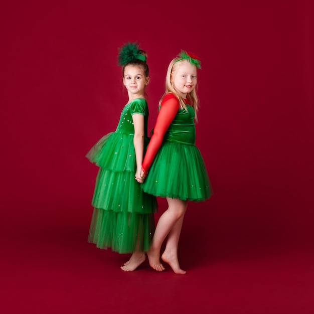 Schöne kleine mädchenprinzessinnen tanzen im grünen luxuskleid lokalisiert auf roter wand. karnevalsparty mit kostümen