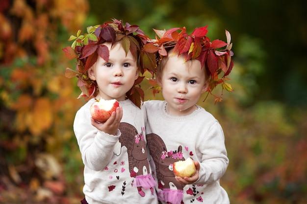 Schöne kleine zwillingsmädchen, die äpfel im herbstgarten halten kleine mädchen, die mit äpfeln spielen