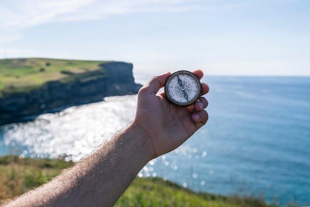 Schöne klippen und offene meereslandschaft mit altem kompass auf der hand des reisenden.