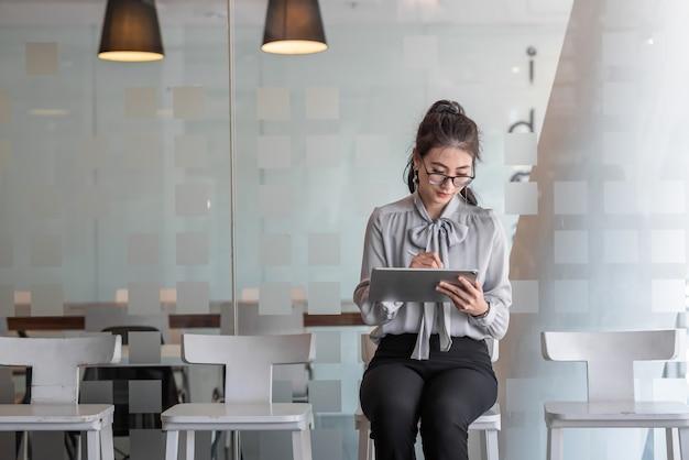 Schöne kluge asiatische geschäftsfrau, die notizen auf der tablette in seinem stuhl sitzend im büro macht. asia frau wartet auf vorstellungsgespräch.
