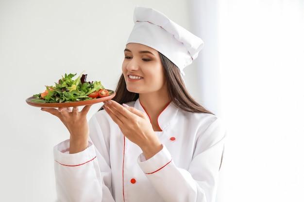 Schöne köchin mit salat in der küche