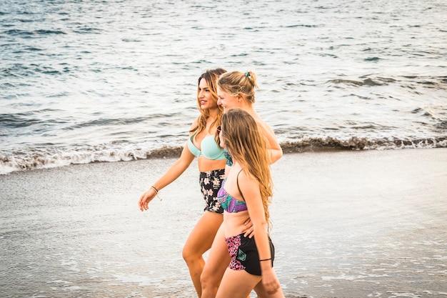 Schöne körper junge frauenmodelle, die zusammen in freundschaft am ufer in der nähe des ozeans für die sommerferienfreizeit gehen