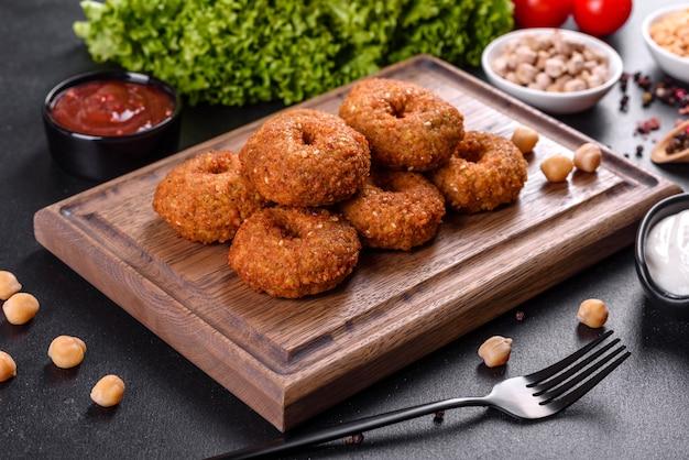 Schöne köstliche frische kichererbsenfalafel mit saucen auf einem konkreten hintergrund. elemente der vegitären küche