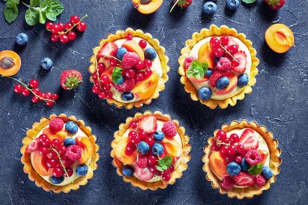 Schöne köstliche sommertörtchen mit frischer vanillepudding-cremefüllung, belegt mit himbeeren, aprikosen, heidelbeeren, erdbeeren, roten johannisbeeren auf einem betontisch mit zutaten, flatlay